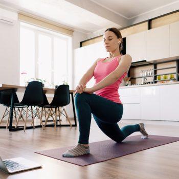 caucasian-woman-practicing-yoga-home-min